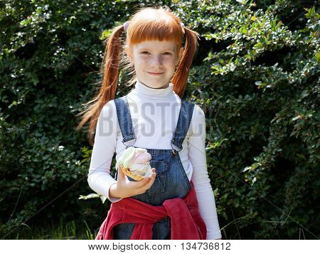 The little red-haired girl in blue jeans with freckles holds a cake with cream and smiling broadly greenery background