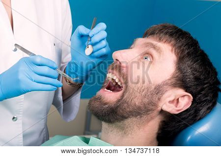 Doctor examines the oral cavity on tooth decay.