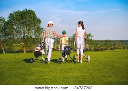 Family golfers plaing golf at sunny day, back view