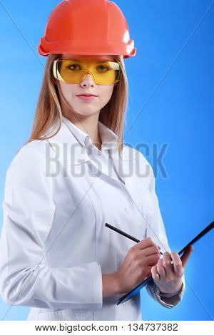 Young attractive doctor isolated over blue background