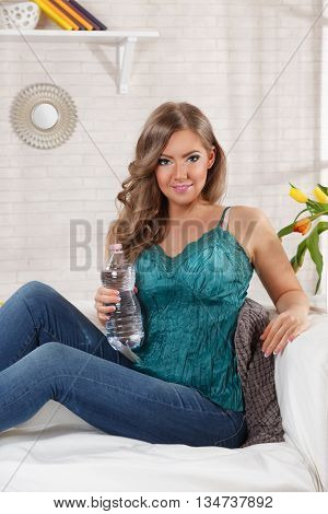 Pretty woman drinking water from a bottle on the couch