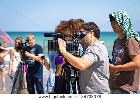 Odesa, Ukraine - June 4, 2016: TV camera man filming a beach sport event, windsurfing competition