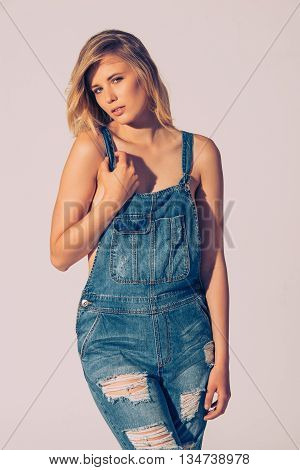 Denim style. Studio shot of beautiful young woman in jeans overall looking at camera