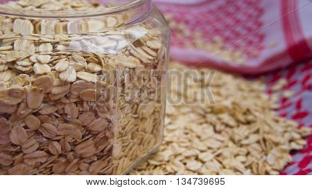 porridge crude lies in a bottle on a cloth, flakes of porridge are scattered by a row, fabric of white and red color,
