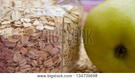 porridge crude lies in a bottle on a cloth, flakes of porridge are scattered by a row, fabric of white and red color, nearby green apple, one