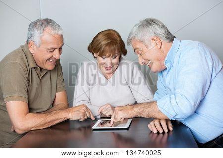 Senior Classmates Watching Man Using Digital Tablet At Desk