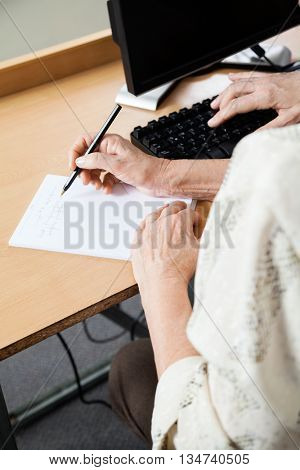 Senior Woman Writing Notes In Computer Class
