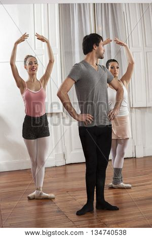 Mid Adult Man Training Ballet Dancers In Studio