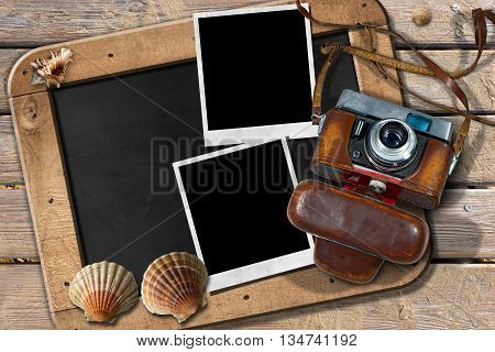 Vintage camera with leather case two empty instant photo frames and a blank blackboard on a wooden boardwalk with sand and seashells