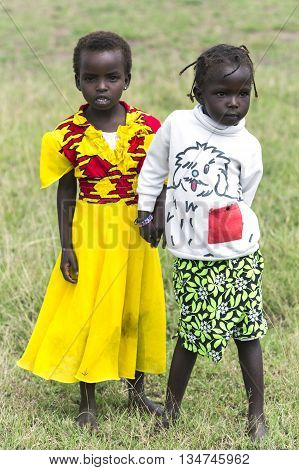 AFRICA, KENYA, MAY, 05, 2016 - Two African girls in the savannah at Masai Mara National Park, Kenya, Africa