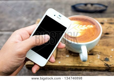 Smartphone with cup of latte art milk coffee leave texture on wooden background Clos up business object