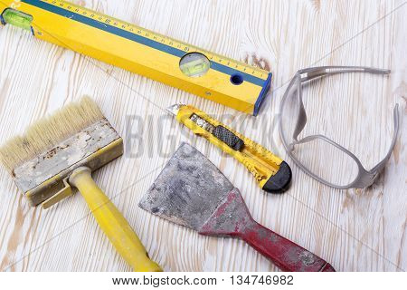 Construction tools: level, trowel, glasses, knife and brush on wooden background