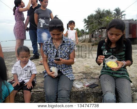 CEBU CITY, CEBU / PHILIPPINES - JULY 30, 2011: People enjoy eating sliced pineapple at a picnic at the seashore of Cebu.