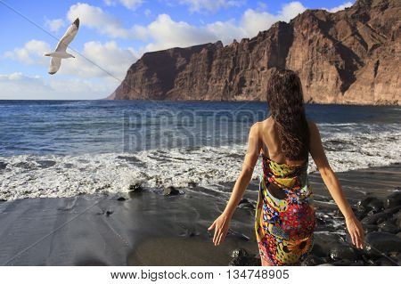 Beautiful brunette girl standing on the beach of Los Gigantes in Tenerife with black sand, mountains and flying seagull