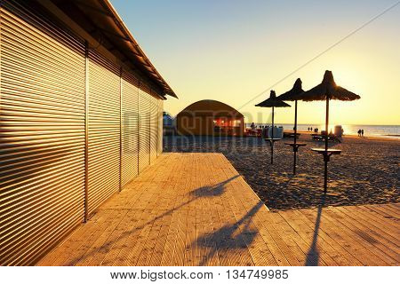 Wooden terrace with beach umbrellas and a cafe in the sunlight and promising lines at sunset with vacationers people