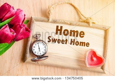 Home Sweet Home on house wooden board shape with red tulip flower with red candle heart shape on wooden background.