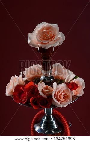 Asian hookah decorated with flowers on dark background
