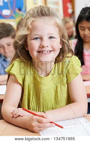 Portrait Of Female Elementary School Pupil Working At Desk