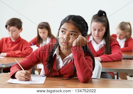 Unhappy Female Pupil Finding School Exam Difficult
