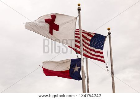DALLAS, USA - APR 9: Flags of the USA State of Texas and Red Cross waving in the wind. April 9, 2016 in Dallas, Texas, United States
