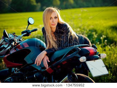 Sexy fashion female biker girl. Blonde woman in leather jacket sitting on vintage custom motorcycle. Outdoors lifestyle portrait.