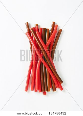 strawberry and cola candy sticks on white background