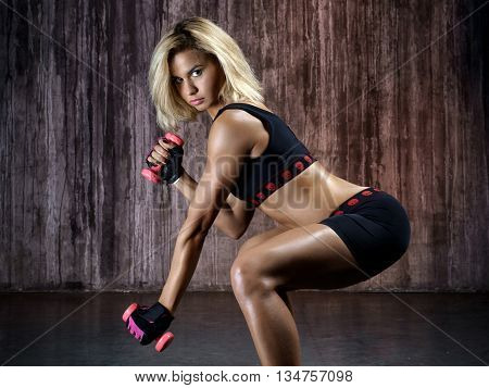 Beautiful muscular woman doing exercise with dumbbells on a gray background in studio. The side view of sexy young blonde woman workout in the grange gym.
