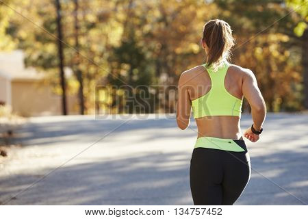 Caucasian woman jogging on country road, back view close up