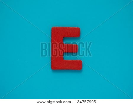 Capital letter E. Red letter E from wood on blue background. Alphabet vowel.