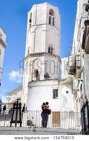 Monte Sant Angelo Italy August 17 2014: a young couple hugging under the white Angioina tower