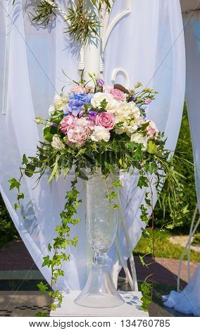 elegant bouquet of roses and hydrangeas in a vase on a light background