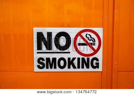 Color image of a no smoking sign on a wall.