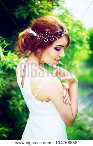 beautiful woman with decoration in her hair in the summer park