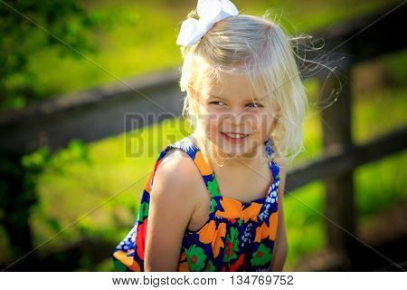 Blonde caucasian girl playing outside in cute dress by wooden bridge