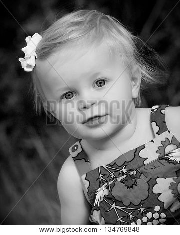 Cute toddler sitting in flowered dress outside in grass black and white