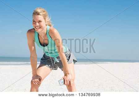 Young happy athlete tired after exercising. Woman resting at beach and listening to music after a routine workout. Young woman enjoying music at beach after run.