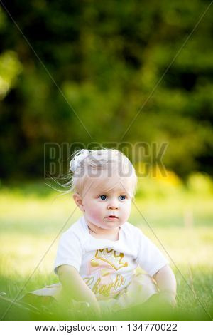 Serious beautiful blonde haired toddler girl sitting alone outside in grass at park
