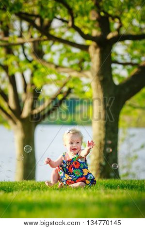 Blonde toddler girl sitting and playing in park by lake at sunset with bubbles