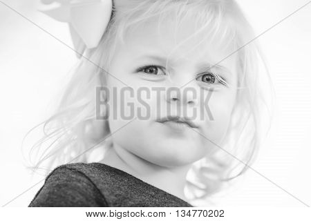 portrait of young girl with blonde curls. Black and white.