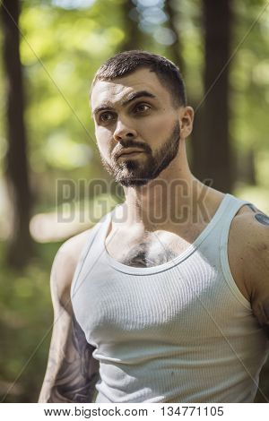 portrait of aggressive muscular guy posing in forest