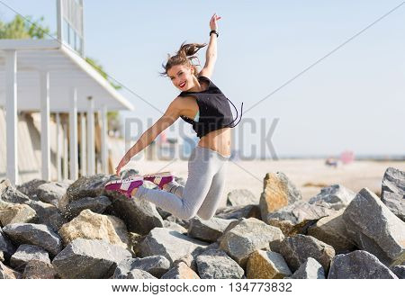 Woman Working Out And Jumping At The Summer Beach