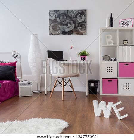 Spacious interior with bed desk chair and shelving unit with flooring