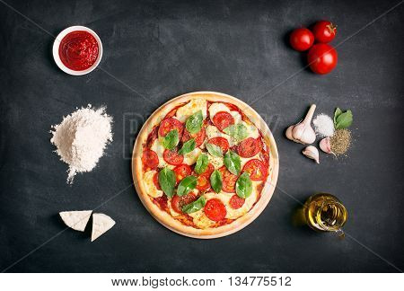Pizza (margherita) and ingredients on the chalk board with copy space