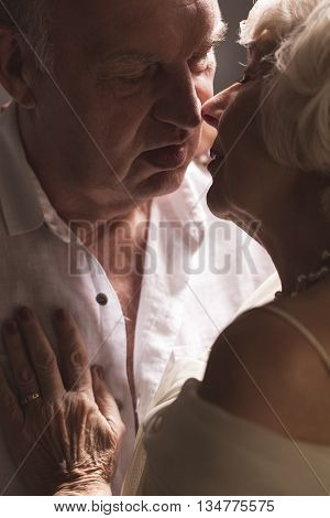 Close up of senior couple kissing with passion