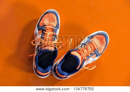 Top Down View Of Orange And White Badminton Sport Shoes On The Orange Floor