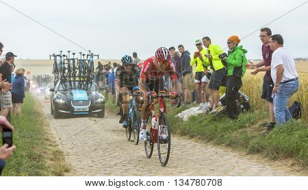 Quievy, France - July 07 2015: Lars Bak (Lotto-Soudal Team) and Ian Stannard (Team Sky) riding on a cobblestoned road during the stage 4 of Le Tour de France 2015 in Quievy France on 07 July2015.