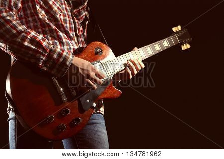 Young man playing electric guitar on lighted dark background