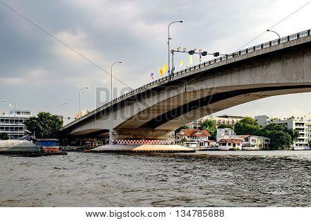 Bridge over the Chao Phraya river in dark sky Bangkok Thailand.