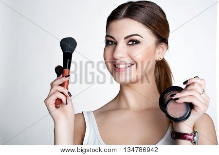Beauty smiling happy Girl make up artist with Makeup Brush. Bright Holiday Make-up for Brunette Woman with Brown Eyes. Beautiful Face. Makeover. Perfect Skin. Applying Makeup
