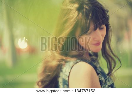 photo with artistic blurring and blur effect. special defocused effect. vintage toning. film retro style. outdoor portrait of a young beautiful woman. soft focus